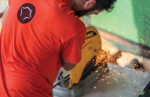 black mesa security installation technician using saw